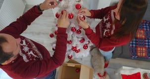 Gelukkig paar die in Kerstmiskleren witte Christmass-boom verfraaien stock video