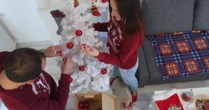 Gelukkig paar die in Kerstmiskleren witte Christmass-boom verfraaien stock footage