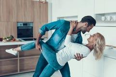 Gelukkig paar die in keuken dansen Romantische verhouding stock foto's