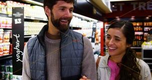 Gelukkig paar die in kruidenierswinkelsectie lopen stock videobeelden