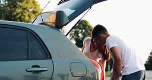 Gelukkig paar die in liefde voor de Bagage van de Vakantielading in Auto weggaan Vakantieconcept, de zomertijd stock videobeelden