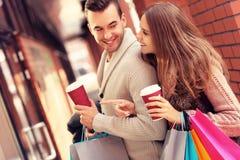 Gelukkig paar die met koffie in de wandelgalerij winkelen stock afbeeldingen