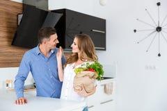 Gelukkig paar die met pakket van producten op keuken flirten Stock Afbeelding
