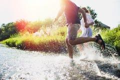 Gelukkig paar die in ondiep water lopen Stock Afbeeldingen