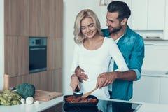 Gelukkig paar die ontbijt samen in keuken voorbereiden royalty-vrije stock fotografie