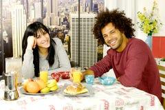 Gelukkig paar die ontbijt voor wolkenkrabbers in stad hebben die camera kijken Royalty-vrije Stock Fotografie