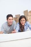 Gelukkig paar die op de vloer liggen en een huisplan houden Stock Afbeelding