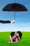 Gelukkig paar die op gras onder paraplu liggen Stock Afbeeldingen