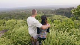 Gelukkig paar die op groene bergpiek koesteren en van mooi landschap genieten Man en vrouw die op groene heuvel omhelzen en stock video