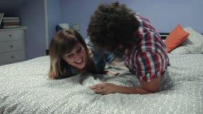Gelukkig paar die op het bed kietelen stock videobeelden