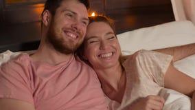 Gelukkig paar die op TV in bed thuis letten bij nacht stock videobeelden