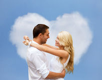Gelukkig paar die over hart gevormde wolk koesteren Stock Afbeelding