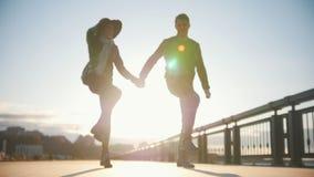 Gelukkig paar die pret hebben in openlucht - het mannetje en de vrouw dansen bij slow-motion zonsondergang, stock video