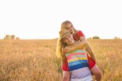 Gelukkig paar die pret in openlucht op tarwegebied hebben Het concept van de vrijheid piggyback stock foto's