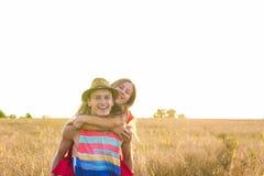 Gelukkig paar die pret in openlucht op tarwegebied hebben Het concept van de vrijheid piggyback stock foto