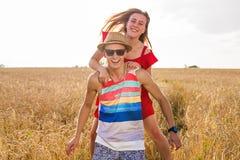 Gelukkig paar die pret in openlucht op tarwegebied hebben Het concept van de vrijheid piggyback royalty-vrije stock afbeelding