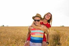 Gelukkig paar die pret in openlucht op tarwegebied hebben Het concept van de vrijheid piggyback royalty-vrije stock foto