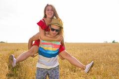 Gelukkig paar die pret in openlucht op tarwegebied hebben Lachende Blije Familie samen Het concept van de vrijheid piggyback royalty-vrije stock foto's