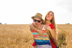 Gelukkig paar die pret in openlucht op tarwegebied hebben Lachende Blije Familie samen Het concept van de vrijheid piggyback royalty-vrije stock fotografie