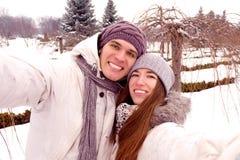Gelukkig paar die selfie op een datum in park in de winter doen Royalty-vrije Stock Afbeelding