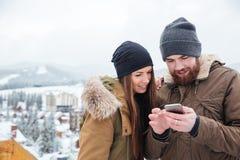 Gelukkig paar die smartphone samen in de winter gebruiken Royalty-vrije Stock Afbeeldingen