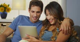Gelukkig paar die tussen verschillende rassen tablet samen op laag gebruiken Royalty-vrije Stock Foto's