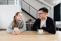 Gelukkig paar die van een koffie genieten bij de koffiewinkel stock afbeelding