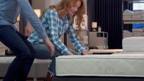 Gelukkig paar die voor nieuw bed bij meubilairopslag winkelen stock video
