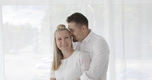 Gelukkig paar die voor venster koesteren stock video