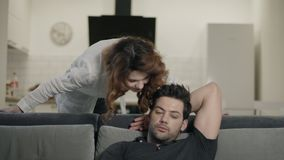 Gelukkig paar die in woonkamer glimlachen Vermoeide mens die op TV op bank letten stock video