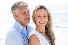 Gelukkig paar die zich door het overzees bevinden en elkaar koesteren Stock Foto