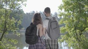 Gelukkig paar die zich op riverbank in het bos met rugzakken bevinden die weg richten De jonge man en vrouwen wandeling stock videobeelden