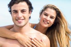 Gelukkig paar die in zwempak camera en het omhelzen bekijken Royalty-vrije Stock Afbeelding