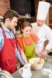 Gelukkig paar en het mannelijke chef-kokkok koken in keuken Stock Afbeeldingen