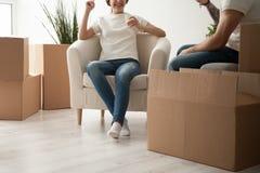 Gelukkig paar het drinken sap in nieuwe flat terwijl het uitpakken van doos stock foto's