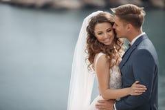 Gelukkig paar in liefde met de bruidegom en de bruid tegen de achtergrond van de bergen dichtbij de blauwe oceaan Royalty-vrije Stock Afbeeldingen