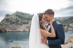 Gelukkig paar in liefde met de bruidegom en de bruid tegen de achtergrond van de bergen dichtbij de blauwe oceaan Stock Foto's