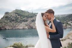 Gelukkig paar in liefde met de bruidegom en de bruid tegen de achtergrond van de bergen dichtbij de blauwe oceaan Stock Afbeeldingen