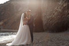 Gelukkig paar in liefde met de bruidegom en de bruid tegen de achtergrond van de bergen dichtbij de blauwe oceaan Royalty-vrije Stock Foto