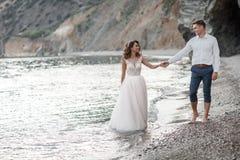 Gelukkig paar in liefde met de bruidegom en de bruid tegen de achtergrond van de bergen dichtbij de blauwe oceaan Royalty-vrije Stock Afbeelding