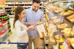 Gelukkig paar met boodschappenwagentje bij kruidenierswinkelopslag Stock Afbeelding