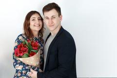 Gelukkig paar met de lentebloemen, witte achtergrond Stock Foto's