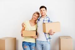 Gelukkig paar met dozen die zich aan nieuw huis bewegen royalty-vrije stock foto