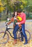 Gelukkig paar met fiets in de herfstpark Stock Foto's