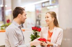 Gelukkig paar met heden en bloemen in wandelgalerij Royalty-vrije Stock Foto's