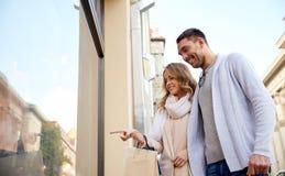 Gelukkig paar met het winkelen zakken bij winkelvenster Royalty-vrije Stock Foto