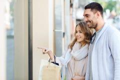 Gelukkig paar met het winkelen zakken bij winkelvenster Stock Foto