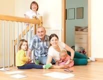 Gelukkig paar met hun nakomelingen en grootmoeder op vloer bij ho Stock Afbeeldingen