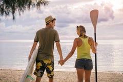 Gelukkig paar met peddelraad op het strand bij zonsondergang Stock Foto's