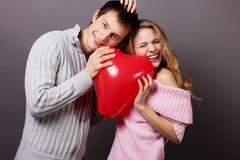 Gelukkig paar met rode ballon. Valentijnskaartendag Stock Afbeelding